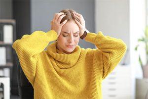 Woman suffering from a severe migraine headache